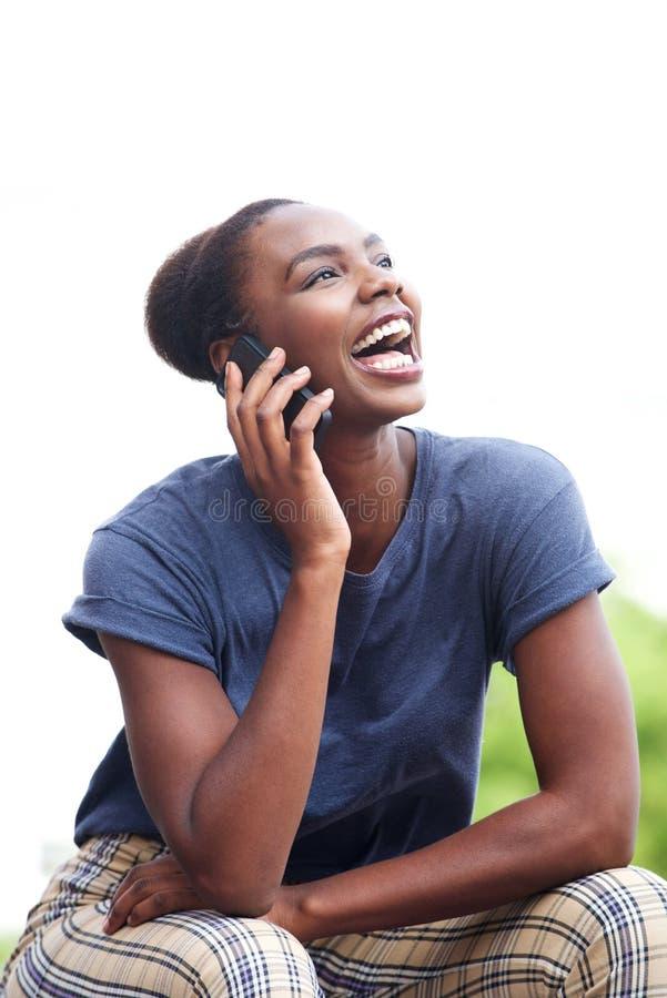 Mulher afro-americano nova atrativa que fala no telefone celular e no riso fotografia de stock royalty free