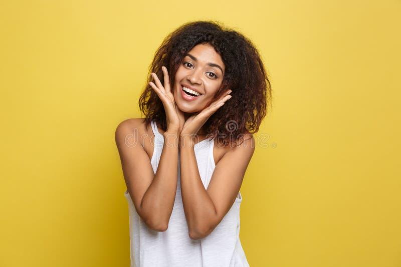 Mulher afro-americano nova bonita de sorriso no t-shirt branco que levanta com mãos no queixo Estúdio disparado no amarelo imagens de stock royalty free