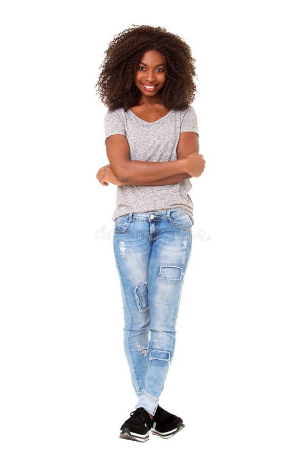 A mulher afro-americano nova bonita do comprimento completo que está com seus braços cruzou-se no fundo branco imagens de stock