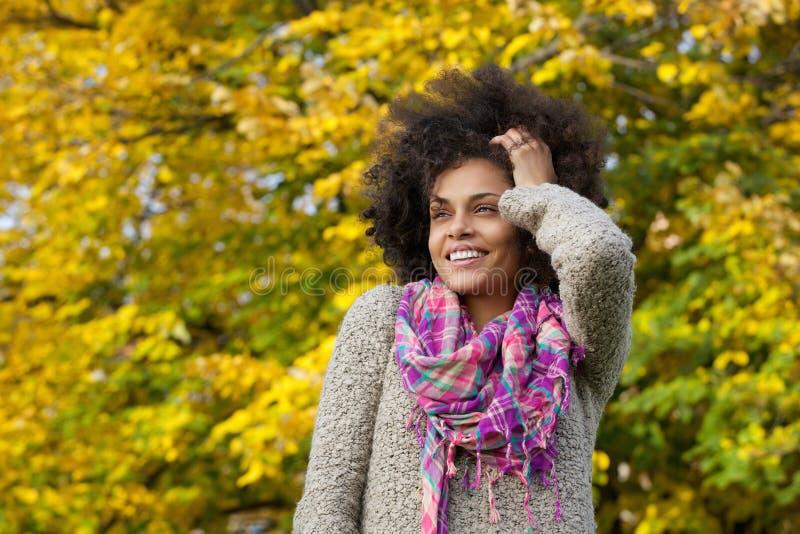 Mulher afro-americano nova bonita que sorri com mão no cabelo fotografia de stock royalty free