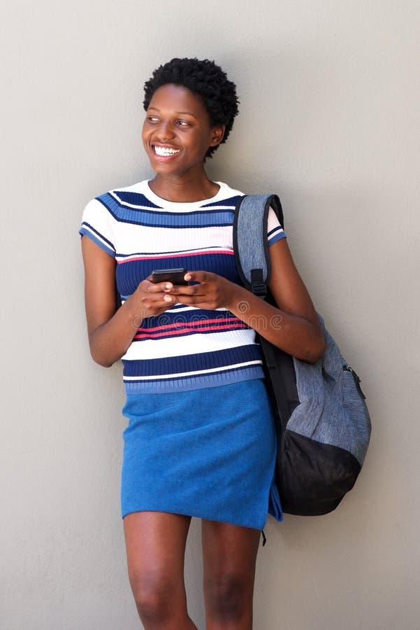 Mulher afro-americano nova com o telefone celular que está contra o fundo cinzento imagem de stock