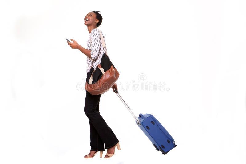 Mulher afro-americano nova feliz do comprimento completo que anda com bagagem e o telefone esperto no fundo branco isolado imagem de stock