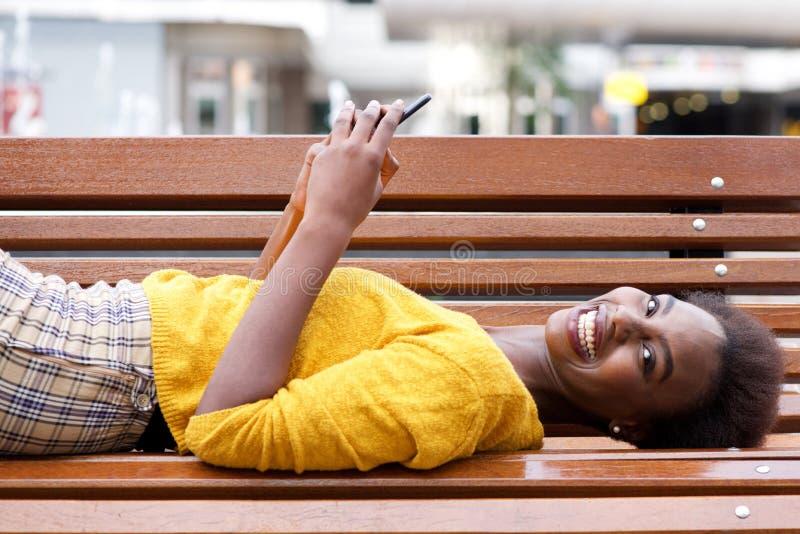 Mulher afro-americano nova feliz que encontra-se no banco com telefone celular fotografia de stock