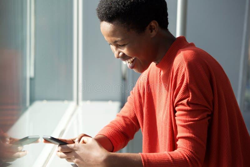 Mulher afro-americano nova feliz que olha o telefone celular pela janela foto de stock