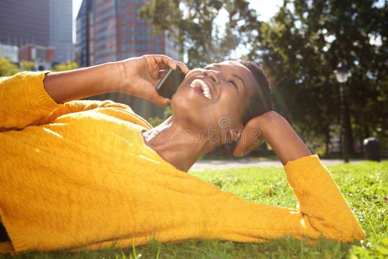 Mulher afro-americano nova feliz que relaxa no parque e que fala com telefone celular imagens de stock