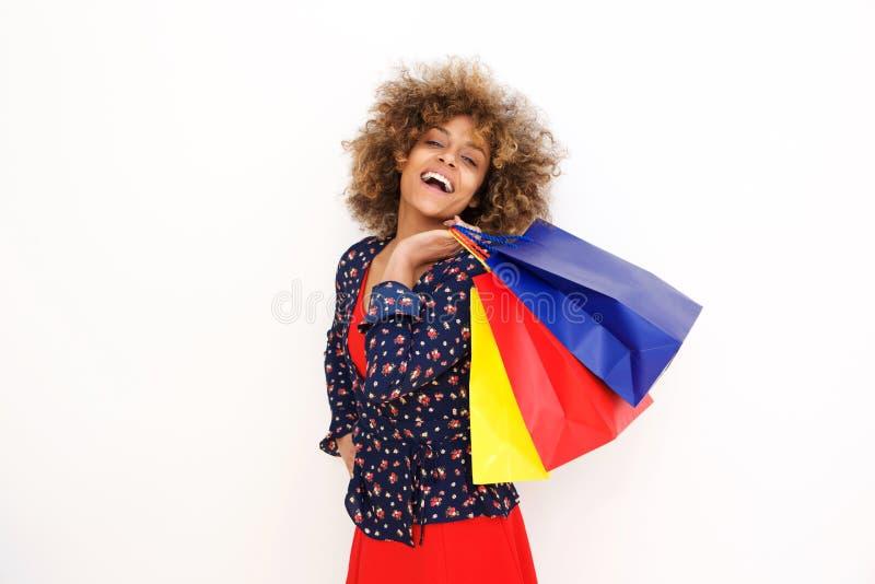 Mulher afro-americano nova na moda com os sacos de compras contra o fundo branco foto de stock royalty free