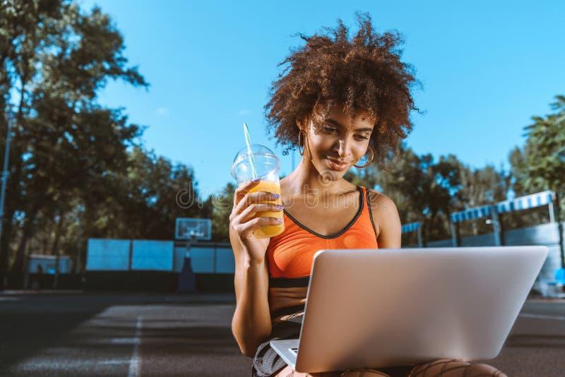 mulher afro-americano nova no sutiã brilhante dos esportes que senta-se na corte do esporte com portátil imagens de stock royalty free