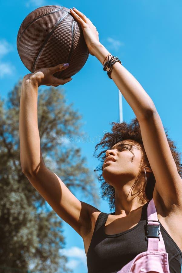 mulher afro-americano nova no sutiã dos esportes e nos macacões cor-de-rosa que jogam a foto de stock