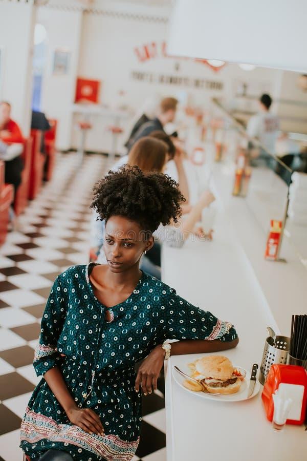 Mulher afro-americano nova que come no jantar fotografia de stock