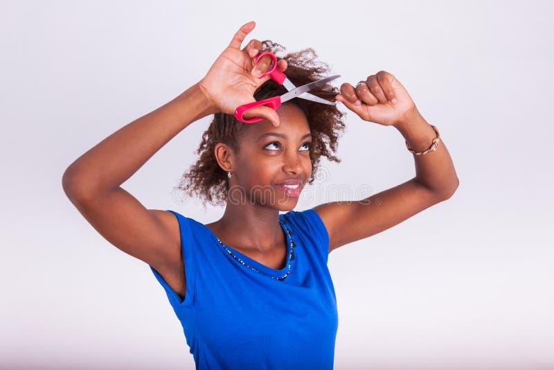 Mulher afro-americano nova que corta seu cabelo afro crespo com s fotografia de stock royalty free