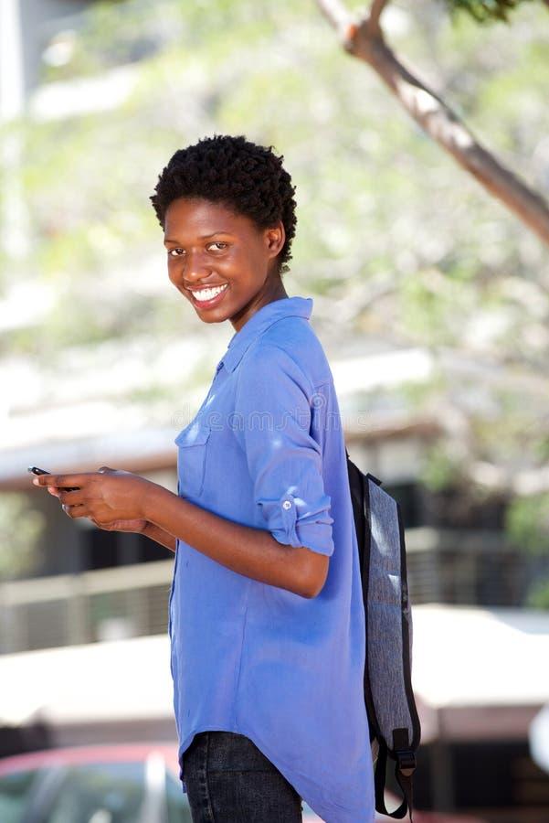 Mulher afro-americano nova que está fora com telefone celular fotos de stock