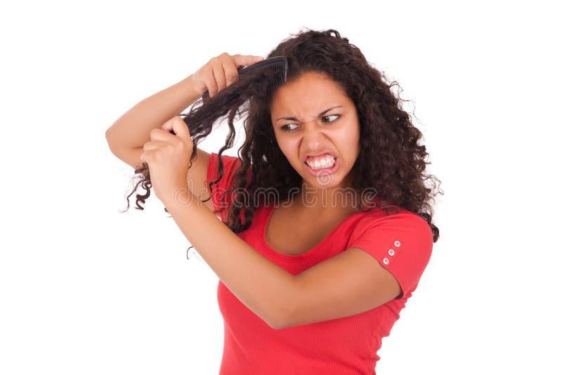 Mulher afro-americano nova que penteia o cabelo imagens de stock