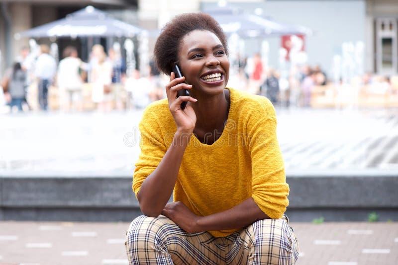 Mulher afro-americano nova que senta-se fora da fala no telefone celular fotografia de stock