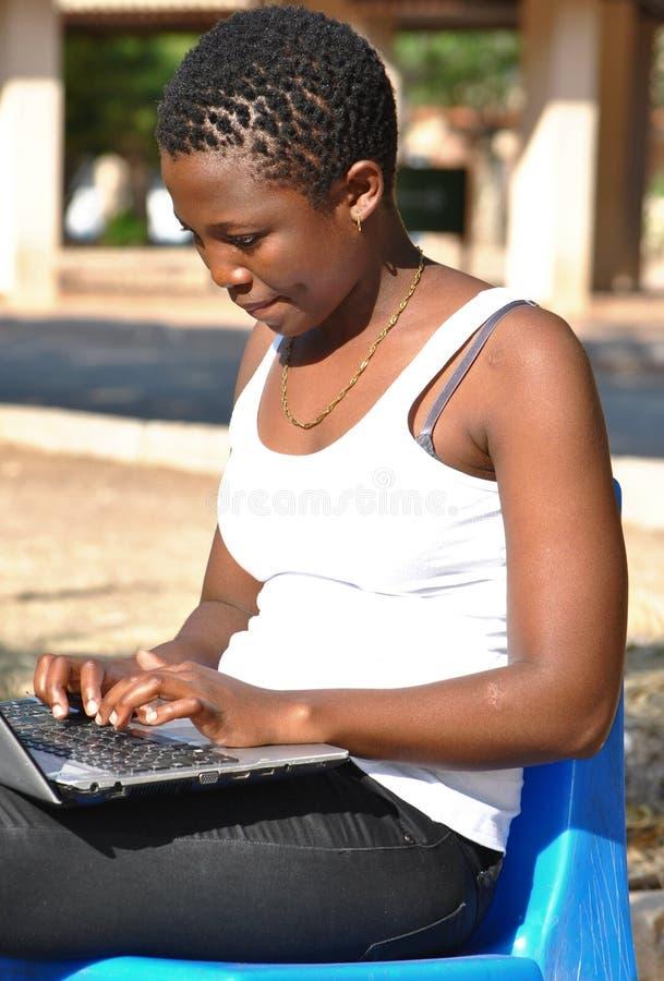 Mulher afro-americano nova que usa o portátil