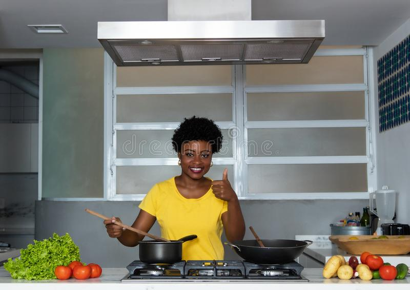 Mulher afro-americano que cozinha na cozinha fotografia de stock royalty free