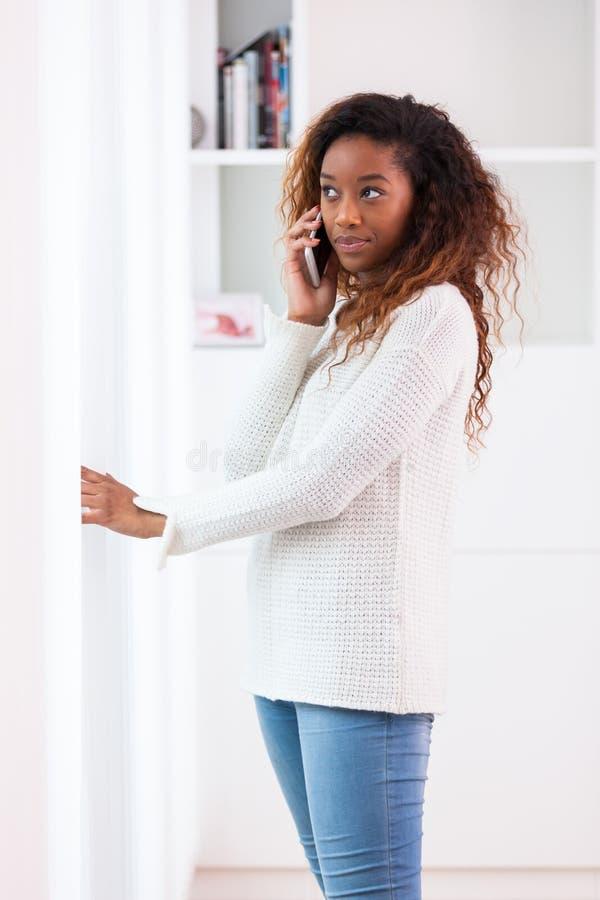 Mulher afro-americano que fala em um telefone celular - pessoas negras fotos de stock royalty free