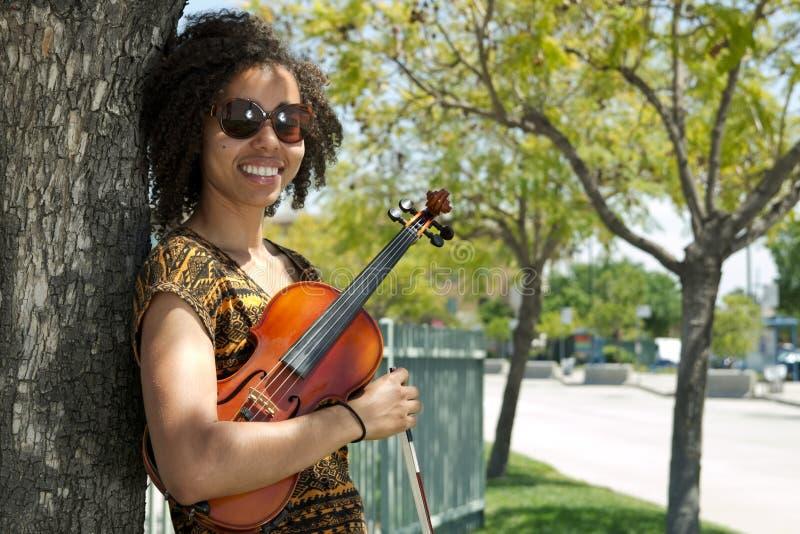 Mulher afro-americano que guarda o violino e que inclina-se contra a árvore fotos de stock royalty free
