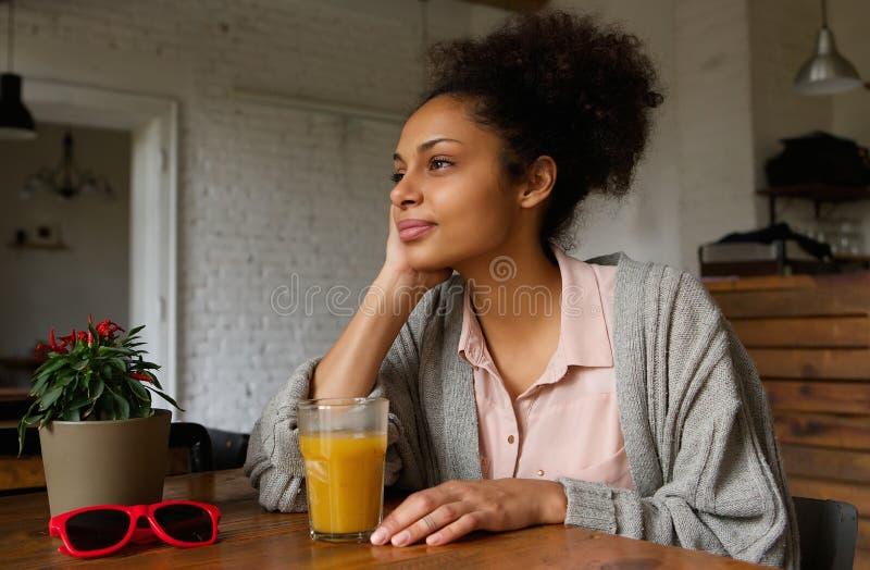 Mulher afro-americano que senta em casa o pensamento imagens de stock royalty free