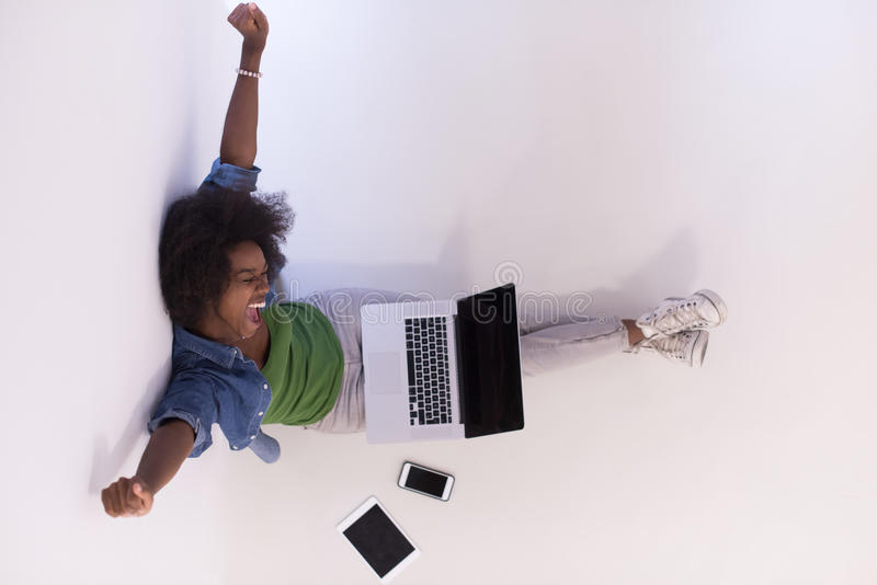 Mulher afro-americano que senta-se no assoalho com opinião superior do portátil foto de stock royalty free