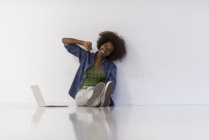 Mulher afro-americano que senta-se no assoalho com portátil imagens de stock
