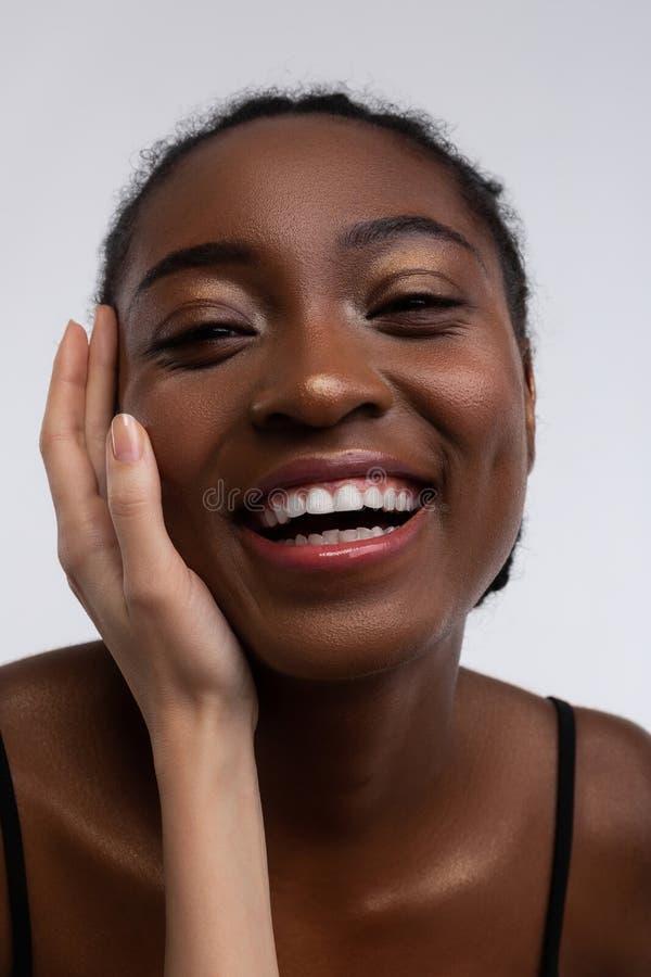 Mulher afro-americano que sorri quando mão branca que toca em sua cara fotografia de stock