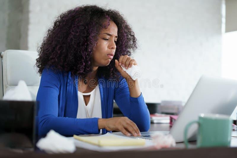 Mulher afro-americano que trabalha em casa tossir e espirrar fotografia de stock royalty free