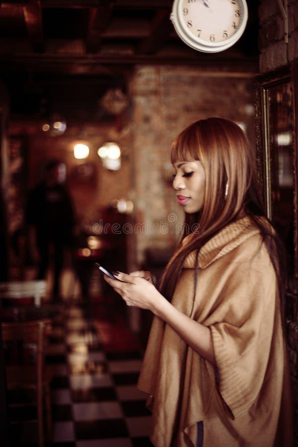 Mulher afro-americano que usa o telefone esperto imagens de stock