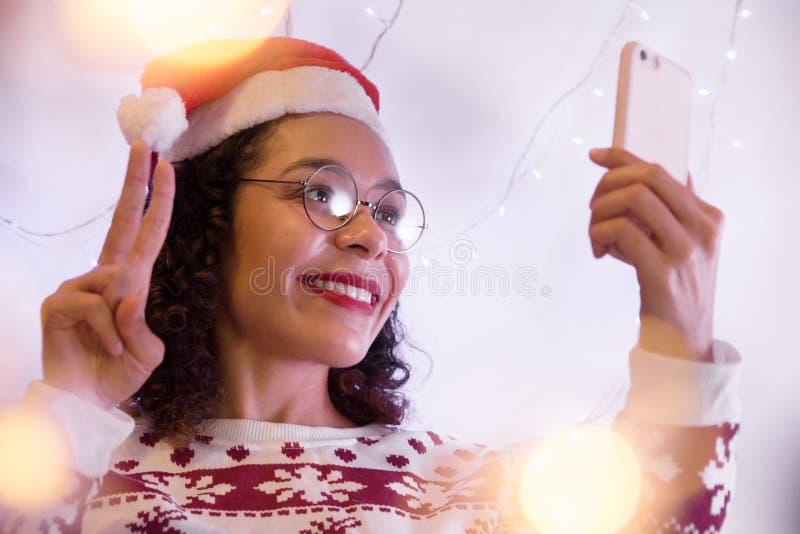 Mulher afro-americano que veste o chapéu de Santa e a camiseta u do Natal foto de stock