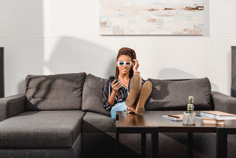 mulher afro-americano relaxado que olha a tevê fotografia de stock
