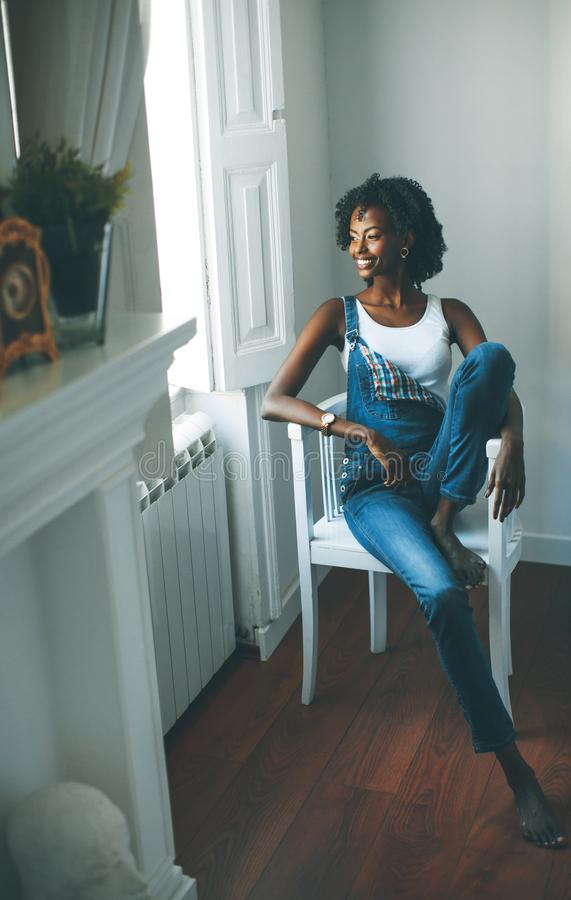 A mulher afro-americano senta-se na sala imagens de stock royalty free