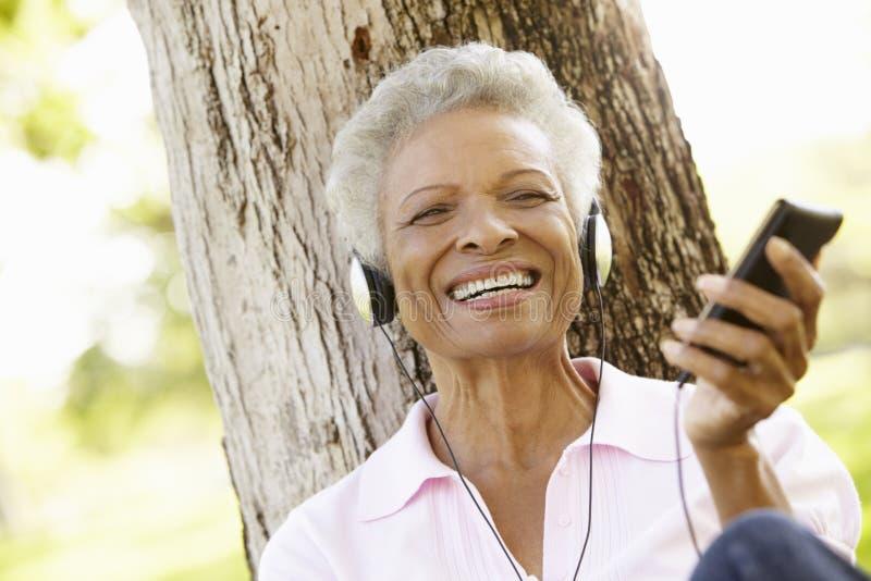Mulher afro-americano superior na escuta o leitor de mp3 fotografia de stock royalty free