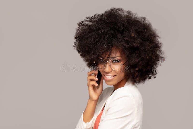Mulher afro bonita que fala pelo telefone celular foto de stock