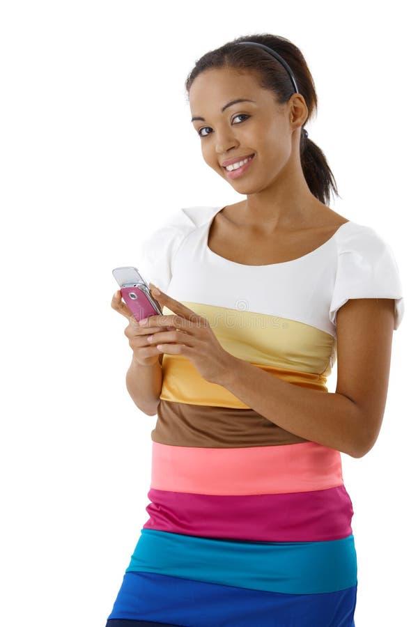 Mulher afro de sorriso que usa o telefone móvel fotos de stock