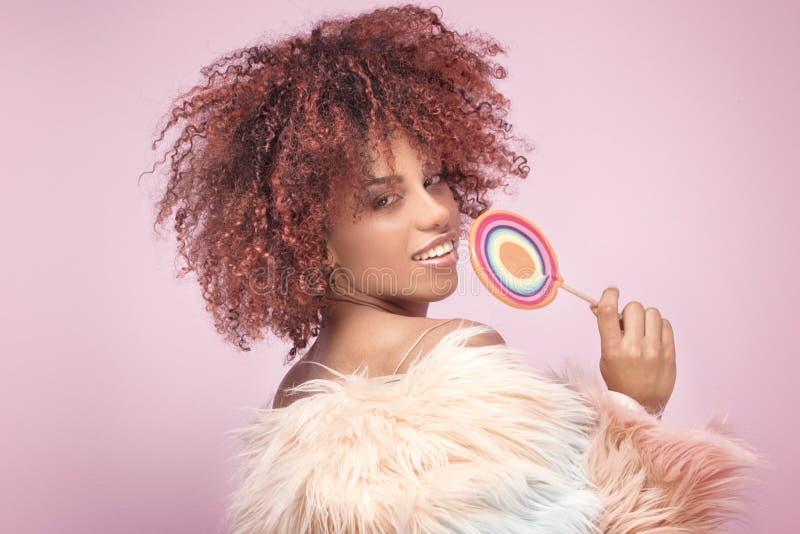 Mulher afro elegante com o pirulito no fundo cor-de-rosa foto de stock