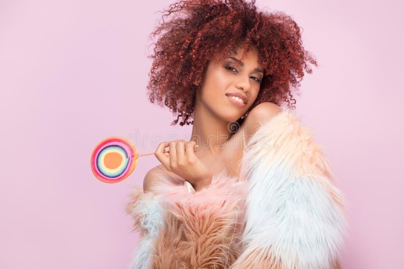 Mulher afro elegante com o pirulito no fundo cor-de-rosa imagem de stock