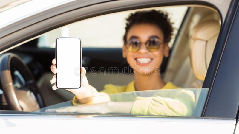 Mulher afro feliz no auto smartphone mostrando com tela vazia imagem de stock royalty free