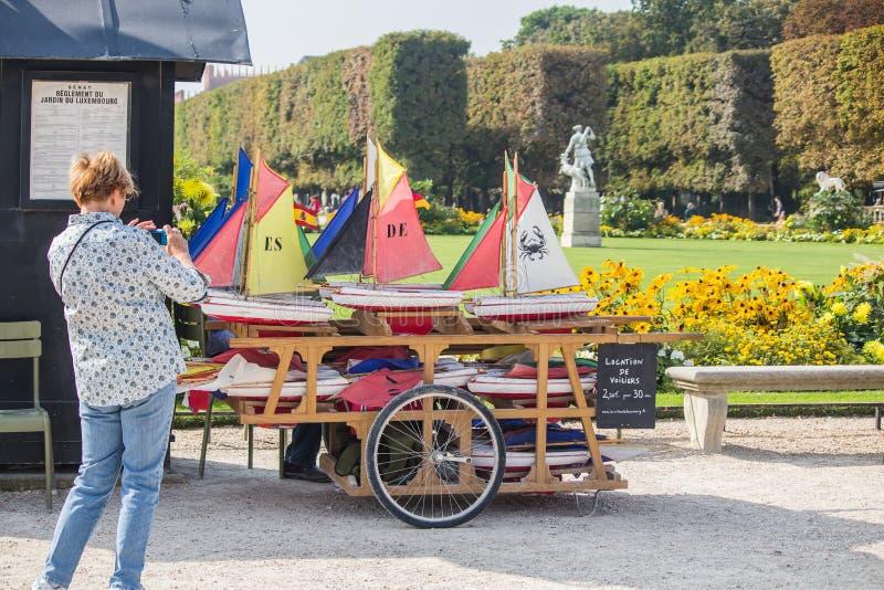A mulher agarra a foto de veleiros do brinquedo no carro no jardim de Luxemburgo, fotos de stock