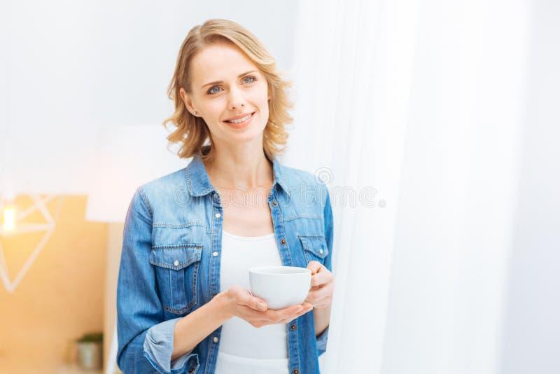 Mulher agradável calma que olha calma ao estar com um copo do chá imagens de stock