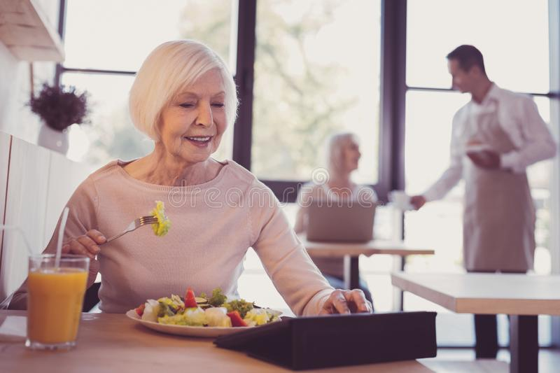 Mulher agradável interessada que come e que trabalha com uma tabuleta fotos de stock royalty free