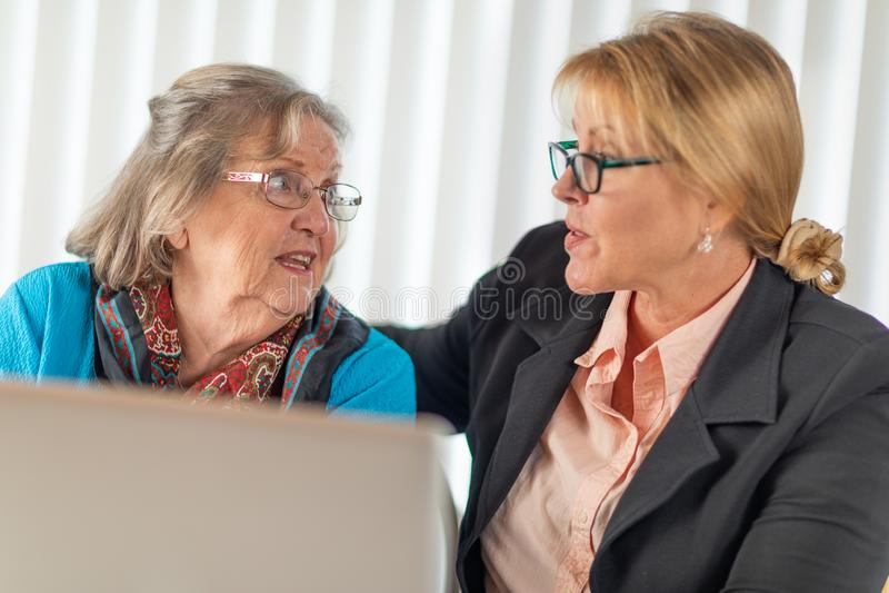 Mulher agrad?vel que ajuda a senhora adulta superior no laptop foto de stock royalty free