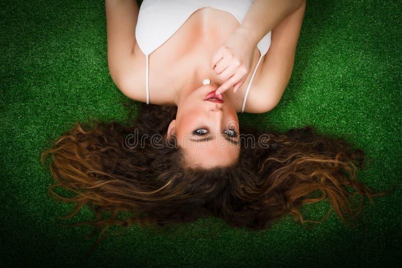 Mulher agradável que fascina na grama fotografia de stock