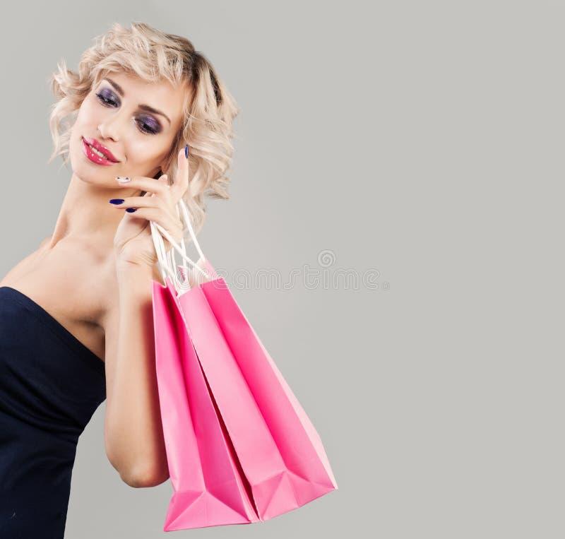 Mulher agradável que guarda sacos de compras cor-de-rosa imagem de stock
