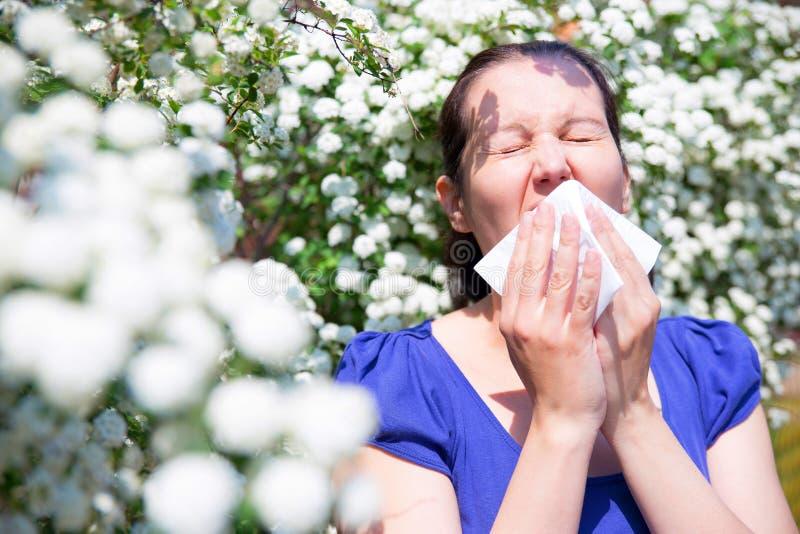 Mulher alérgica que espirra no lenço fotografia de stock royalty free