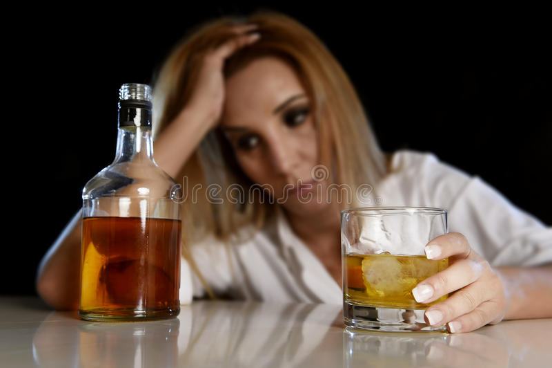 Mulher alcoólica bêbada desperdiçada e comprimida guardando o vidro do uísque escocês que olha pensativo à garrafa imagem de stock