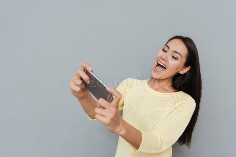 Mulher alegre alegre que joga jogos no smartphone e que tem o divertimento foto de stock