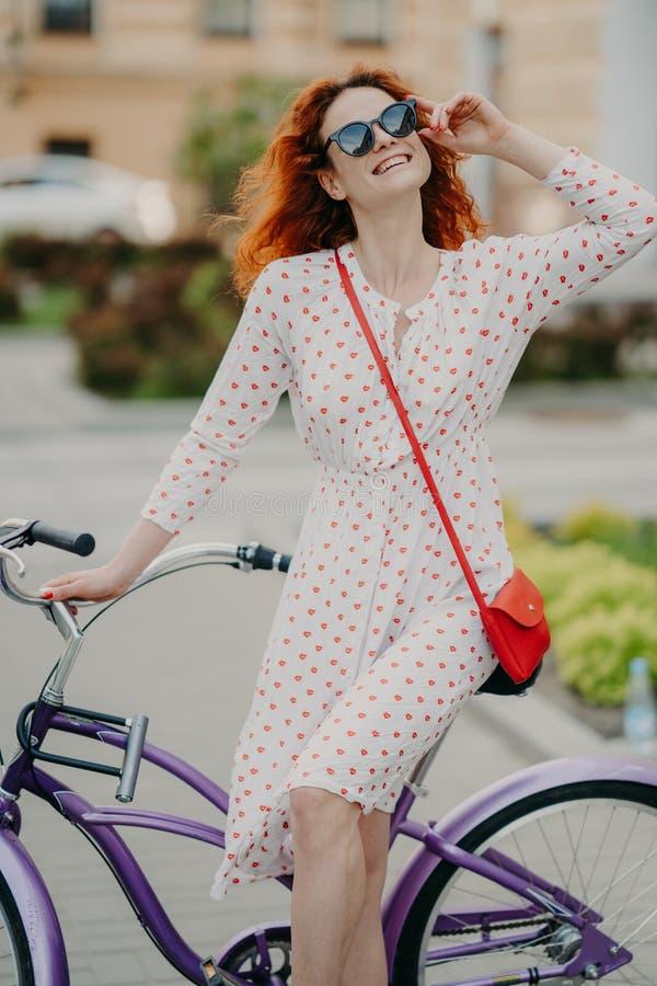 A mulher alegre ativa monta a bicicleta na cidade, veste ?culos de sol ? moda, tem o sorriso encantador toothy, vestido no vestid imagem de stock royalty free