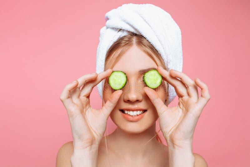 Mulher alegre atrativa com uma toalha envolvida em torno de sua cabeça, guardando fatias do pepino perto de seus olhos, em um fun fotos de stock