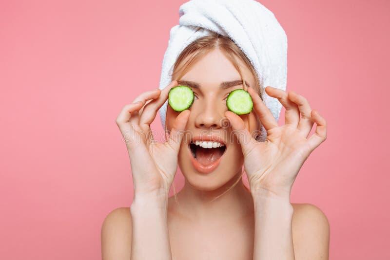 Mulher alegre atrativa com uma toalha envolvida em torno de sua cabeça, guardando fatias do pepino perto de seus olhos, em um fun imagem de stock royalty free