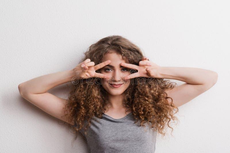 Mulher alegre bonita nova no estúdio, dedos que formam V fotografia de stock