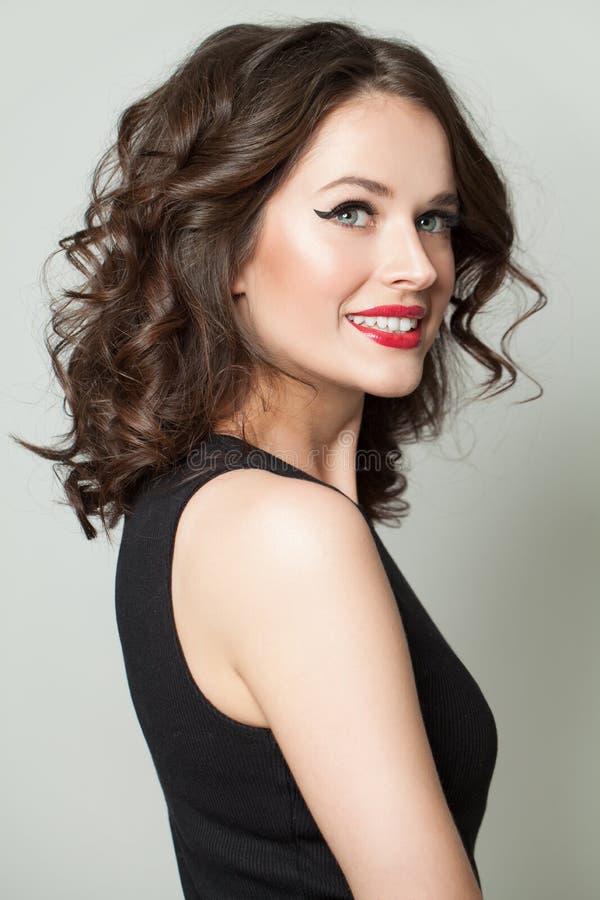 Mulher alegre com composição e cabelo encaracolado Sorriso modelo bonito imagens de stock royalty free